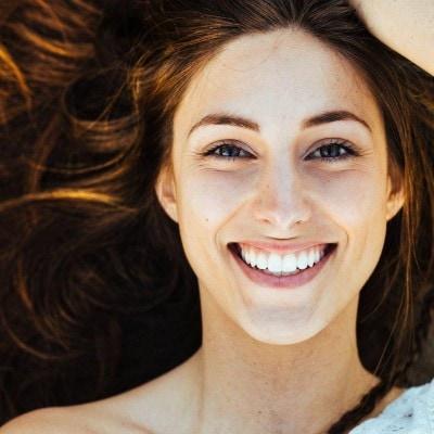 Lachende Frau mit fast unsichtbarer Zahnspange