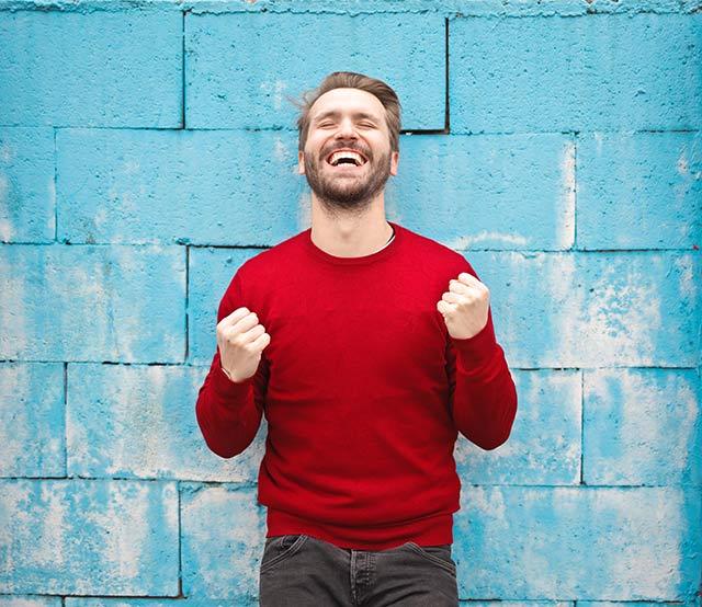 Glücklicher Ilovemysmile Mann mit rotem Pullover mit geraden Zähnen am lachen vor einer blauen Wand